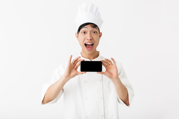 Alegre chefe chinês com uniforme branco de cozinheiro e chapéu de chef segurando o telefone celular isolado sobre a parede branca