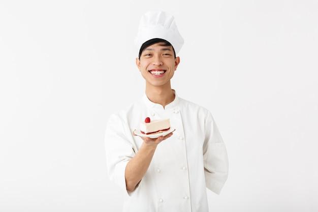 Alegre chefe chinês com uniforme de cozinheiro branco, sorrindo para a câmera enquanto segura o prato com o saboroso cheesecake isolado na parede branca