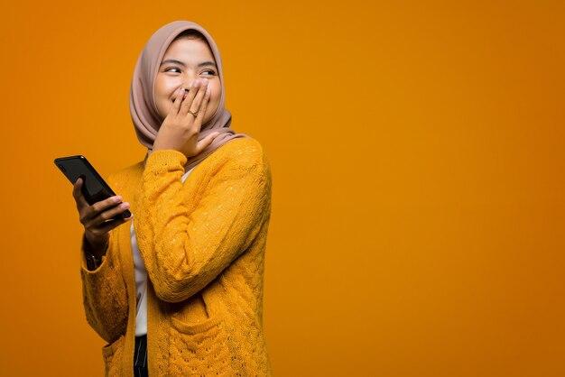 Alegre com a linda mulher asiática segurando um smartphone com um espaço vazio