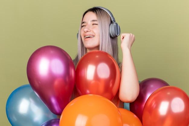 Alegre, com os olhos fechados, uma jovem linda usando aparelho dentário com fones de ouvido em pé atrás de balões