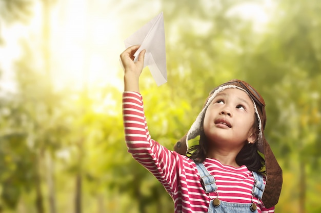 Alegre criança asiática brincando com avião de papel