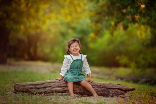 Alegre criança emocional. uma menina senta-se em um tronco em um parque de verão para passear, em torno de árvores verdes.