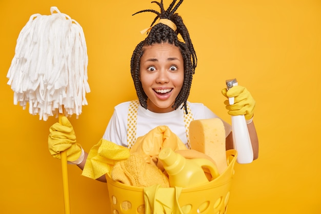 Alegre dona de casa de pele escura segurando detergente químico e esfregão olhando feliz