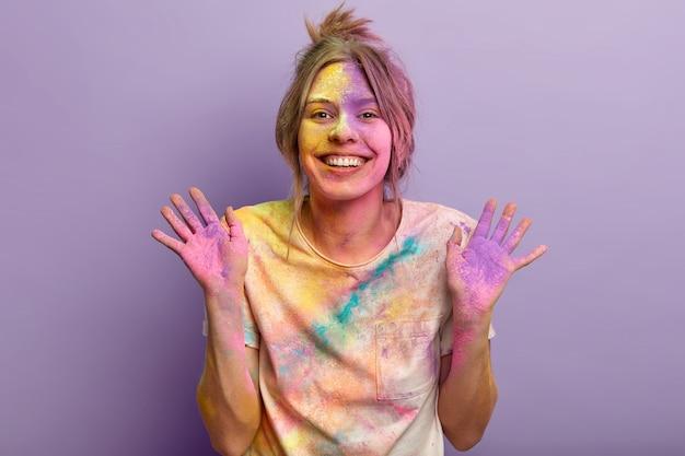Alegre e adorável jovem mostra palmas coloridas, estando de bom humor depois de visitar o festival holi pela primeira vez, brinca com cores, manchada com pó colorido sobre a parede roxa