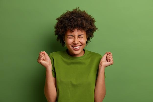 Alegre e alegre adolescente se sente campeã, fecha os punhos em triunfo, se orgulha de suas realizações pessoais, vence competição, fecha os olhos, vestida com uma camiseta verde. emoções e celebração