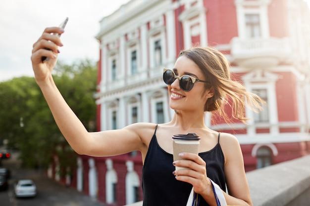 Alegre e alegre garota hispânica de cabelos escuros em óculos de sol, um vestido preto, sorrindo com dentes, tomando selphie na frente do prédio vermelho bonito, bebendo café, passando um bom tempo depois da loja