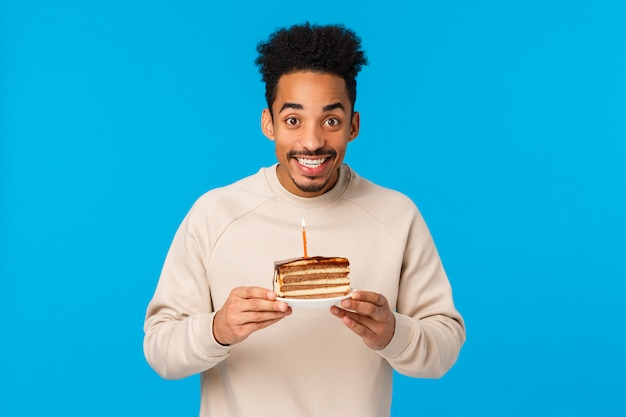 Alegre e animado feliz sorridente afro-americano b-dia comemorando aniversário, segurando o pedaço de bolo com vela, fazendo desejo ancitipating bom ano, em pé parede azul