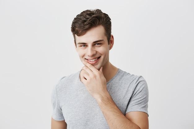 Alegre e bonito macho caucasiano em camiseta cinza mantém a mão sob o queixo, sorri gentilmente, feliz ou satisfeito em ouvir elogios, sente orgulho de si mesmo, tem expressão positiva