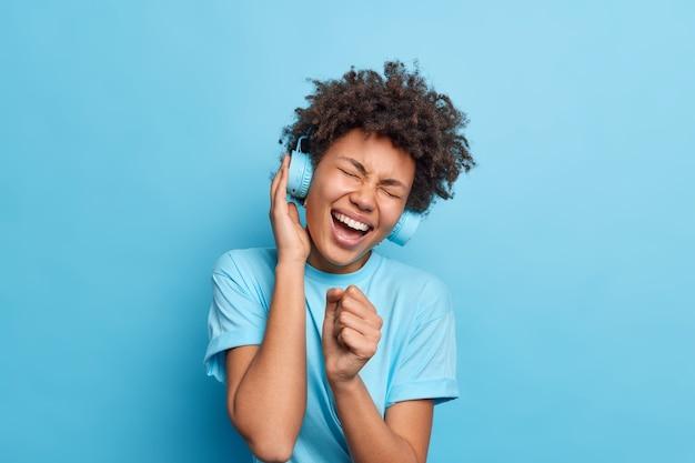 Alegre e cacheada adolescente afro-americana segura a mão perto da boca como se um microfone cantasse sua música favorita em voz alta, usa fones de ouvido estéreo, aprecia a música, usa uma camiseta casual isolada sobre a parede azul