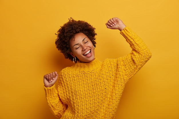 Alegre e charmosa garota de pele escura dança alegremente e comemora boas notícias, se sente com sorte e sucesso