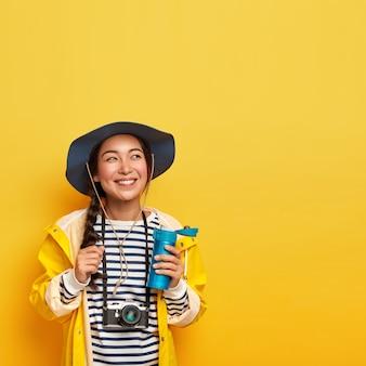 Alegre e descontraída viajante feminina faz uma pausa para o café durante a longa jornada, explora a natureza, segura uma garrafa térmica com bebida, usa câmera retro, macacão listrado e capa de chuva