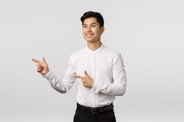 Alegre e determinado jovem empresário asiático decidiu, tomar uma decisão, apontando olhando para a esquerda e sorrindo com aprovação, como o que vê, escolhendo um ótimo produto