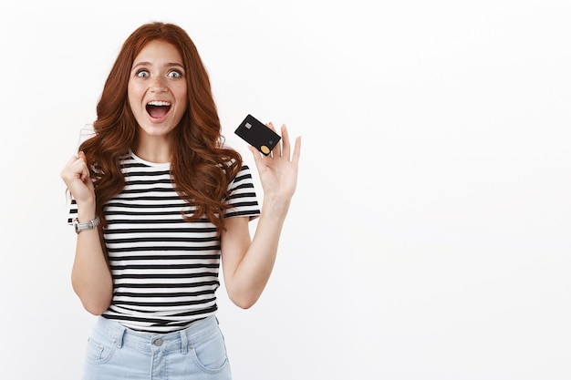Alegre e emocionada linda garota ruiva triunfando, estique o punho com alegria, grite de empolgação e alegria, mostrando o cartão de crédito, reaja ao novo recurso de banco on-line legal, parede branca de pé