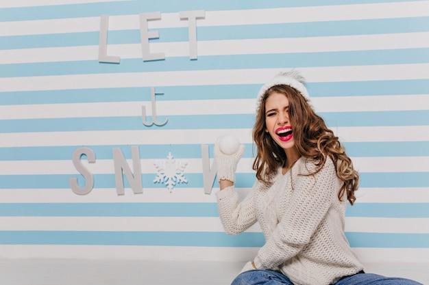 Alegre e encantadora mulher de cabelos compridos de cabelos castanhos joga bolas de neve, sentada no chão com seu suéter de lã quente. modelo rindo posando para retrato em parede listrada