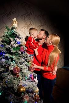 Alegre e feliz mãe, pai e filho de 5 anos no fundo da árvore decorada antes do natal se abraçam. atmosfera acolhedora de natal.