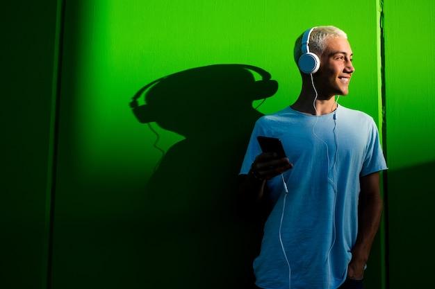 Alegre e feliz milenar se divertindo e curtindo ouvir música com seus fones de ouvido - jovem adolescente ouvindo música e sorrindo com um fundo verde