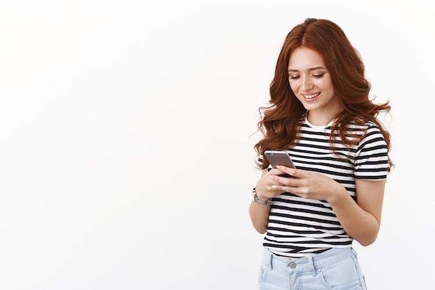 Alegre e fofa ruiva adolescente moderna em uma camiseta listrada, fazendo planos no planejador móvel, use o aplicativo para entrar em contato com amigos, enviar mensagens para a namorada, olhar com alegria na tela do smartphone, sorrindo como se estivesse usando o telefone