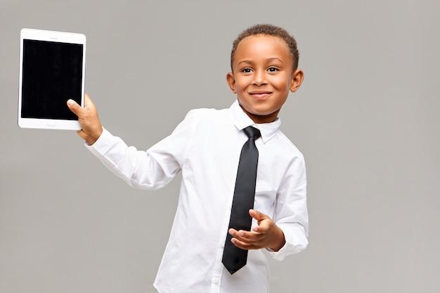 Alegre e fofo estudante afro-americano de camisa e gravata sorrindo alegremente usando um dispositivo eletrônico para jogar ou assistir desenhos animados, segurando um tablet digital com tela em branco com copyspace para seu texto