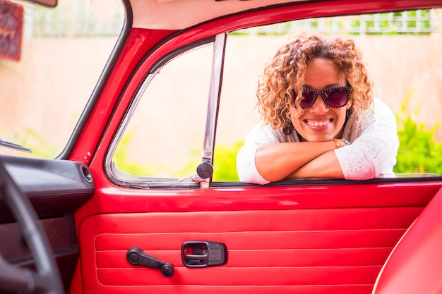 Alegre e linda mulher loira encaracolada de meia-idade caucasiana sorrir e desfrutar da atividade de lazer ao ar livre perto de seu carro clássico vintage vermelho. pronto para viajar e viver o dia