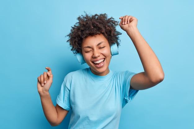 Alegre e relaxada garota afro-americana aprecia sua playlist favorita, ouve música através de fones de ouvido sem fio, levanta os braços vestidos casualmente isolados sobre a parede azul conceito de passatempo e estilo de vida de pessoas