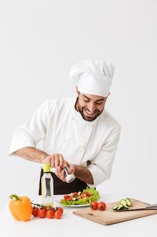 Alegre e satisfeito jovem chef uniformizado, cozinhando com legumes frescos.