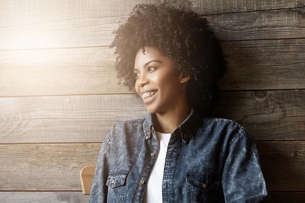 Alegre elegante jovem afro-americana usando aparelho e com uma expressão pensativa e sonhadora