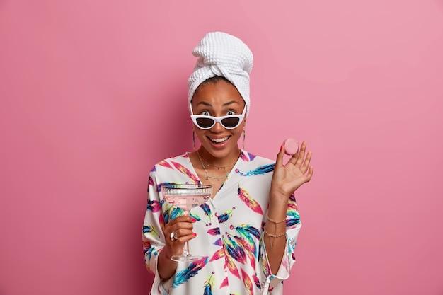 Alegre elegante jovem vestida com manto doméstico e toalha segura copo de macaroon de coquetel usa óculos de sol da moda isolados sobre a parede rosa. conceito de estilo de pessoas