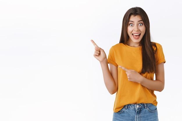 Alegre, emocionada e divertida linda garota participando de incrível sorteio quer ganhar viagem no exterior, apontando canto superior esquerdo, sorrindo divertida e olhando a câmera animada, em pé fundo branco alegre