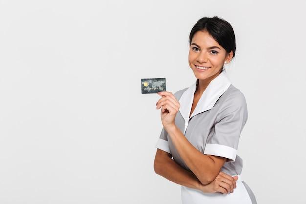 Alegre empregada morena de uniforme segurando o cartão de crédito