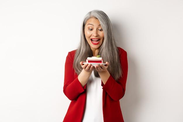Alegre empresária asiática curtindo a festa do escritório, olhando para a deliciosa fatia de bolo e sorrindo, em pé sobre um fundo branco.