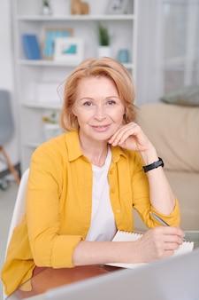 Alegre empresária loira sentada no local de trabalho em frente à câmera e anotando a lista de pontos de trabalho enquanto trabalha em casa