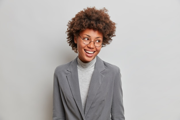 Alegre empresária próspera em elegantes roupas formais cinza, olha feliz para o lado, usa óculos transparentes, sente-se bem-sucedida ao liderar um novo projeto, negócios realizados