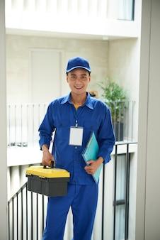 Alegre encanador asiático de macacão em pé na porta com caixa de ferramentas