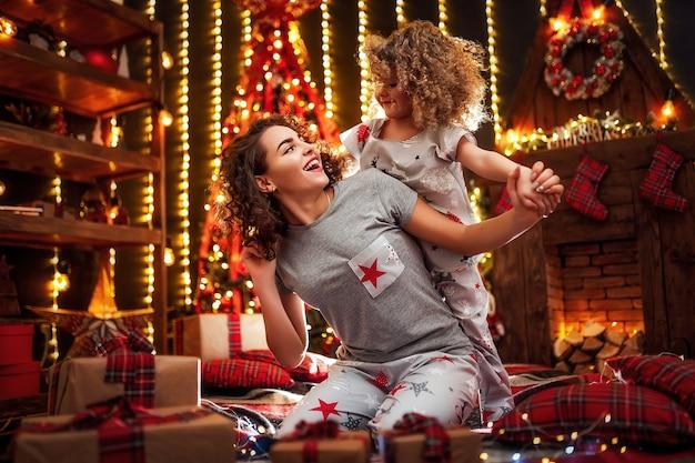Alegre encaracolada menina bonitinha e sua irmã mais velha, trocar presentes.