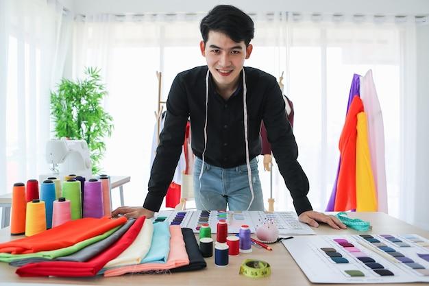 Alegre estilista de roupas masculinas asiáticas em pé à mesa com amostras de têxteis e olhando para a câmera