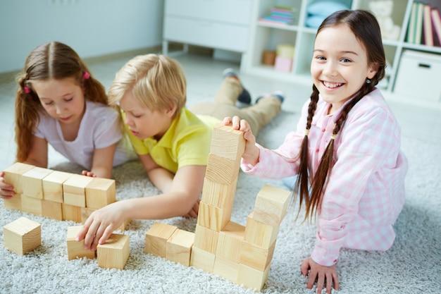 Alegre estudante se divertindo com cubos de madeira