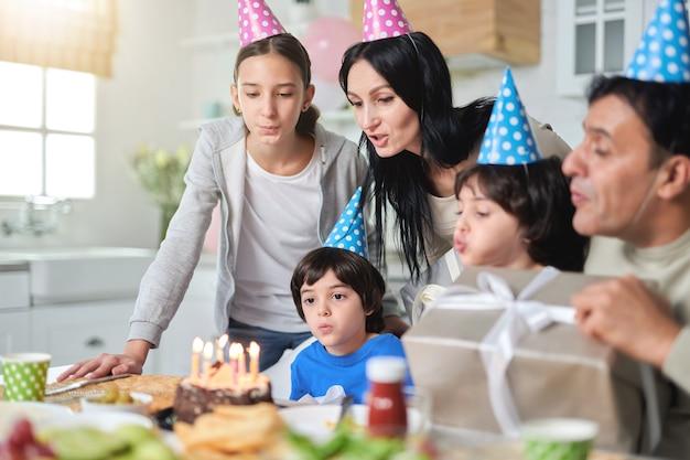 Alegre família latino-americana usando bonés de aniversário, soprando velas em um bolo enquanto comemorava o aniversário juntos em casa. foco seletivo