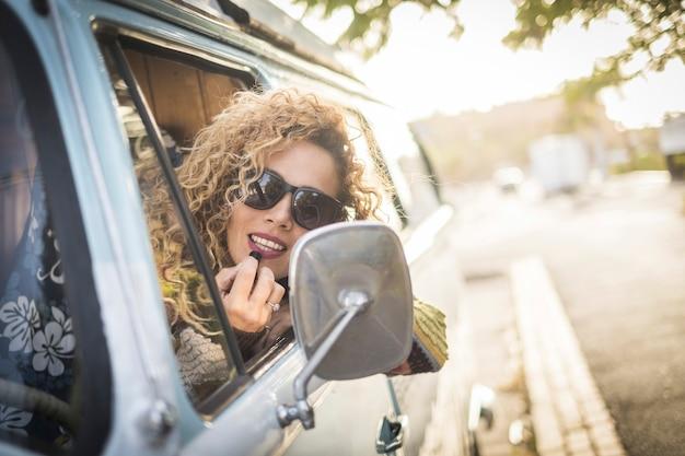 Alegre, feliz e bonita jovem encaracolada verificando a maquiagem do batom com o espelho traseiro de sua van vintage