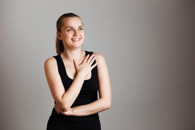 Alegre feliz linda jovem sobre parede cinza. copie o espaço.