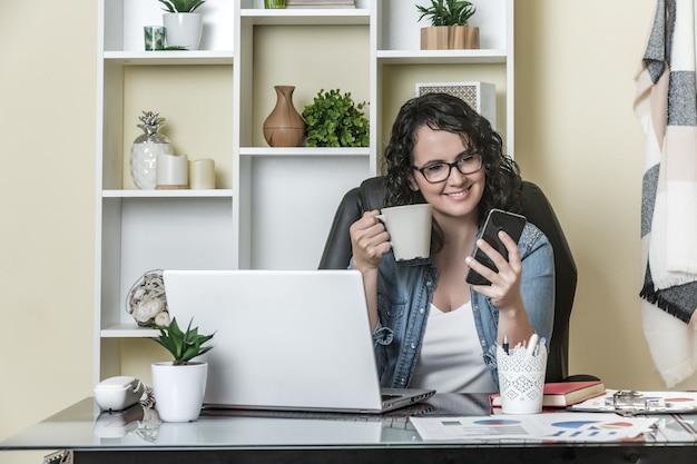 Alegre freelancer bebendo bebida quente e usando smartphone