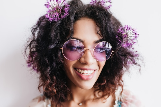 Alegre garota africana com penteado curto, posando com flores roxas. espetacular jovem de óculos escuros usa alliums no cabelo.