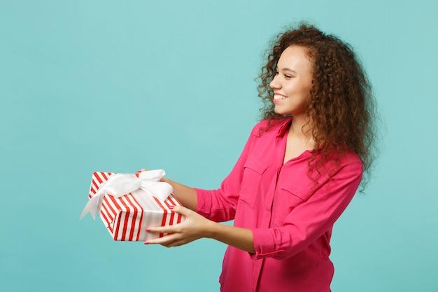 Alegre garota africana em roupas casuais segura caixa de presente listrada vermelha com fita de presente isolada no fundo da parede azul turquesa. conceito de feriado de aniversário do dia internacional da mulher. simule o espaço da cópia.