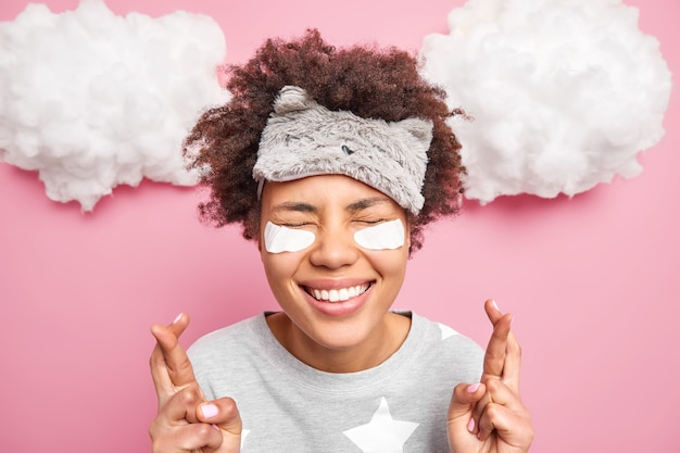 Alegre garota afro-americana encaracolada espera por boa sorte cruza os dedos mantém os olhos fechados sendo supersticiosa faz desejos antes de adormecer usa pijama máscara de dormir adesivos de beleza poses internas