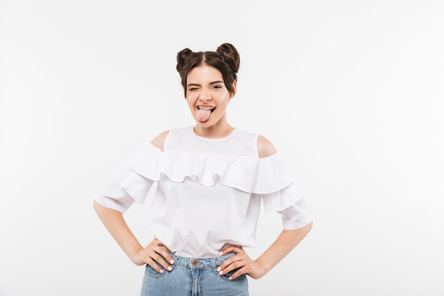 Alegre garota astuta com penteado de pãezinhos duplos, mantendo os braços ao lado do corpo e mostrando a língua para a câmera, isolado no branco