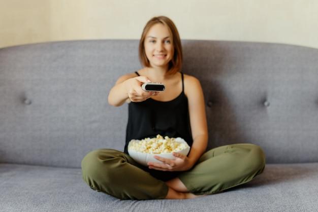 Alegre garota atraente com pipoca, sentado no sofá, assistindo tv, mudando de canal com um controle remoto e comendo pipoca. em casa.