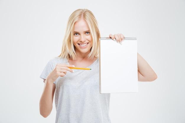 Alegre garota bonita feliz apontando o lápis para o caderno em branco isolado na parede branca