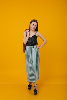 Alegre garota caucasiana, posando com sapatos de salto alto. retrato de uma modelo feminino incrível em um top preto de seda.