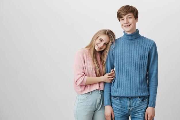 Alegre garota com longos cabelos loiros na camisola rosa com aparelho rindo, abraçando o namorado loiro