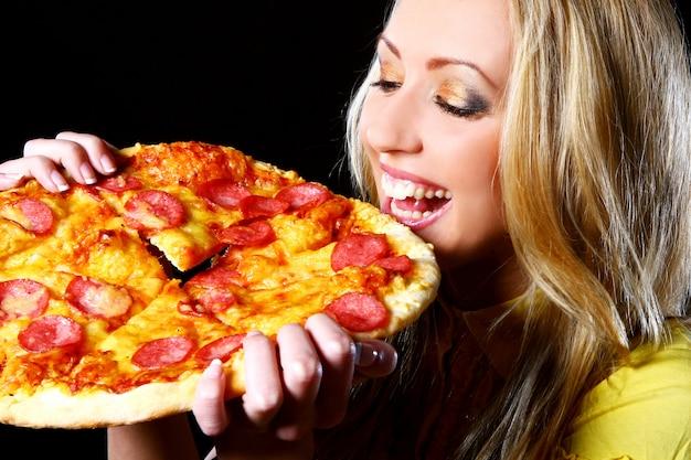 Alegre garota comendo pizza