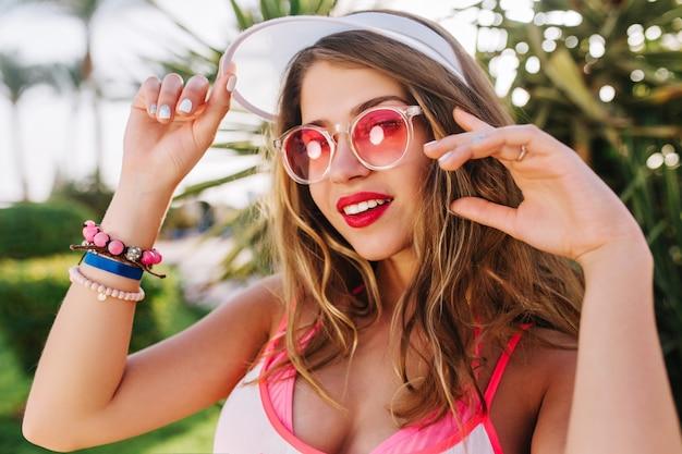 Alegre garota de cabelos compridos com chapéu branco da moda e pulseiras brilhantes, olhando com interesse e posando, acenando com as mãos